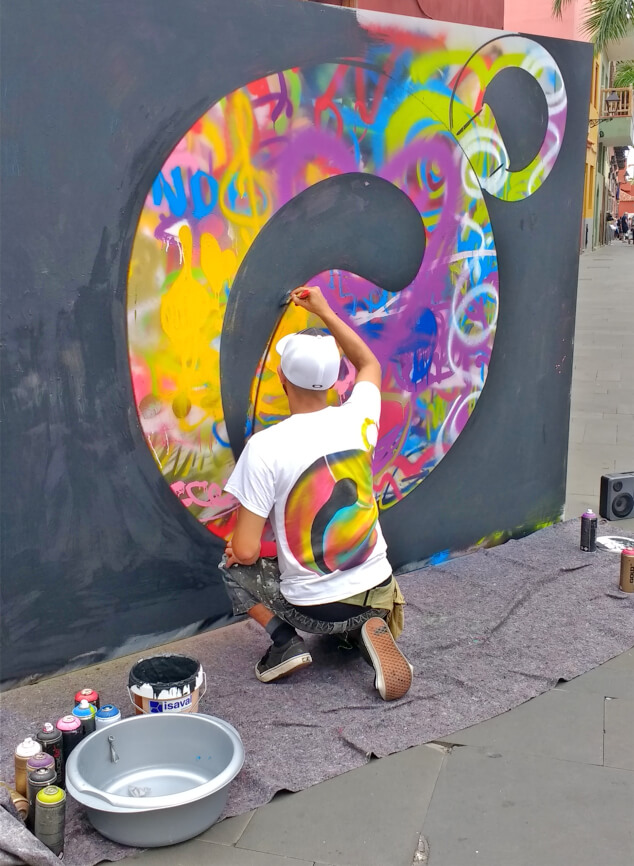 A graffiti artist spray painting at La Mueca
