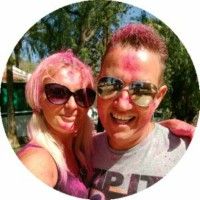 Profile photo of Ian and Nicky covered in pink paint at a festival