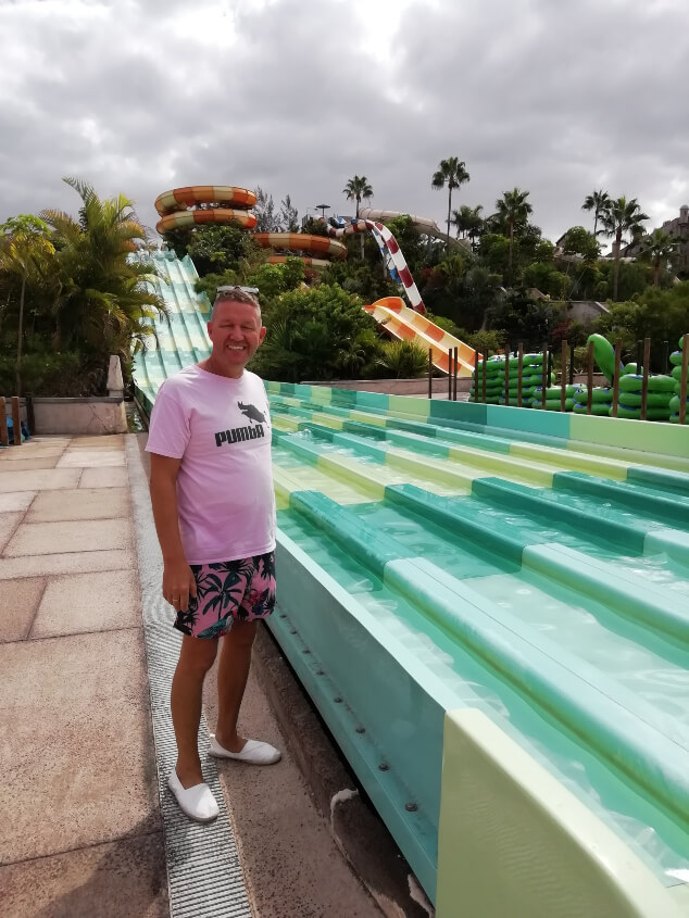 A man in a pink top next to a water slide in Aqualand Tenerife