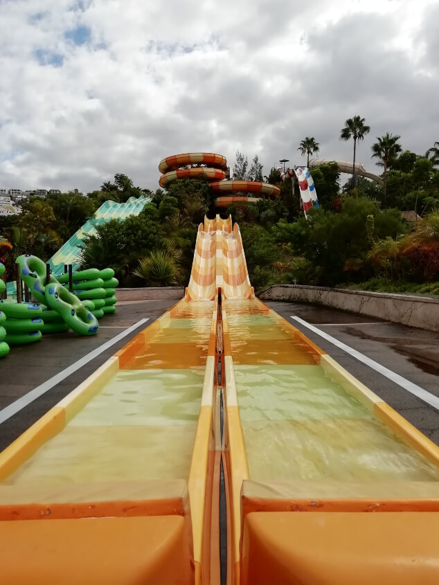 A yellow and orange water slide on a cloudy day