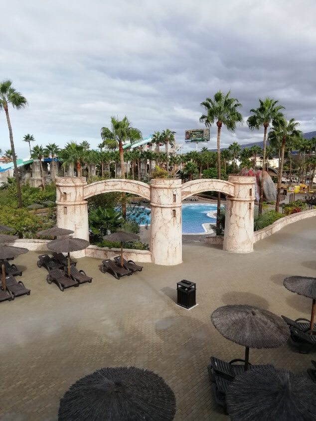 A swimming pool in a water park with a castle theme
