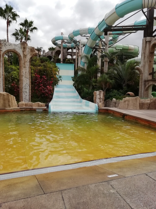 A white and blue water slide going into a yellow pool in Aqualand Tenerife
