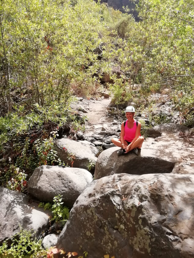 Woman sat on a rock in the Barranco del Infierno walk