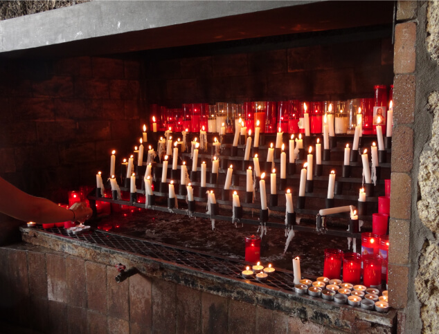 Lit candles inside the Cave of Santo Hermano Pedro in Tenerife