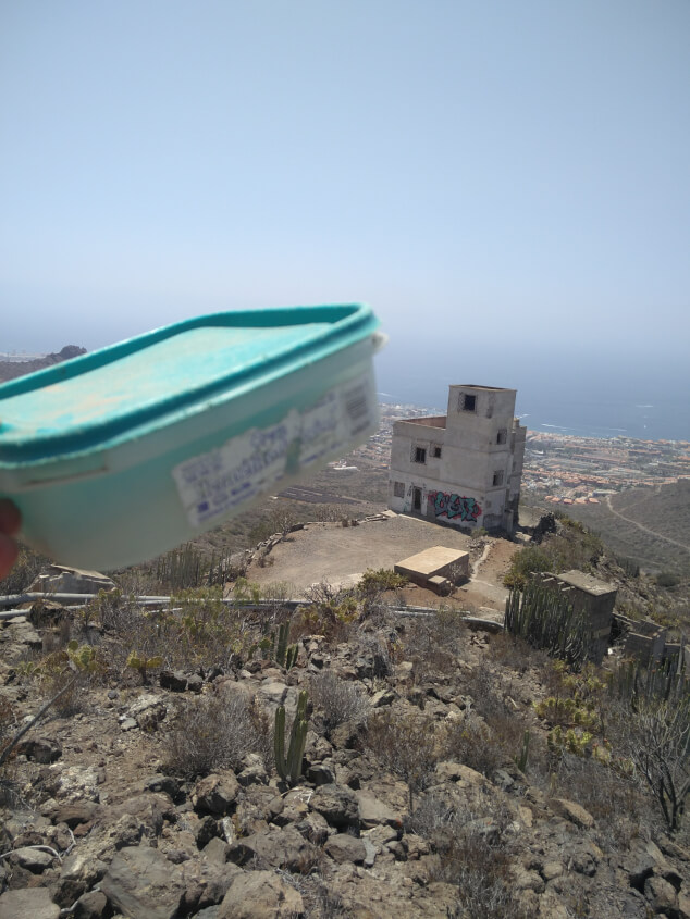A tupperwear box held in front of a sea view found while geocaching in Tenerife