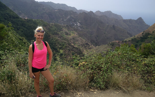 Woman stood in front of a hilly landscape while geocaching in Tenerife