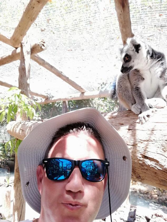 A man taking a selfie with a lemur in Jungle Park Tenerife
