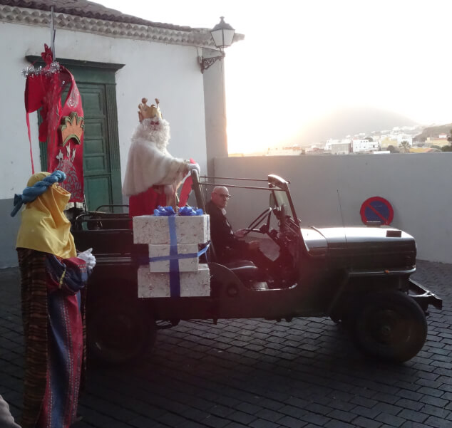 A Jeep with a man dressed up as a king and presents