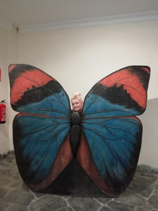 A woman posing as a butterfly at Mariposario del Drago, Tenerife